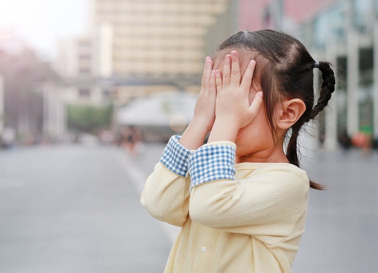 Young girl covering her eyes outside