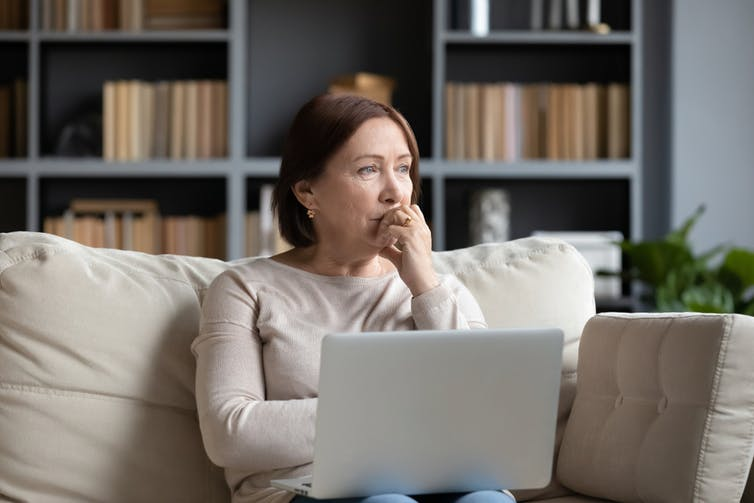 Middle-aged woman sitting on sofa with laptop looking concerned