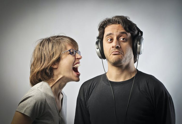 Woman yelling at a man wearing headphones and ignoring her