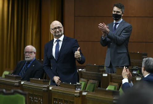 Minister of Justice David Lametti standing, giving thumbs up, as colleagues clap.