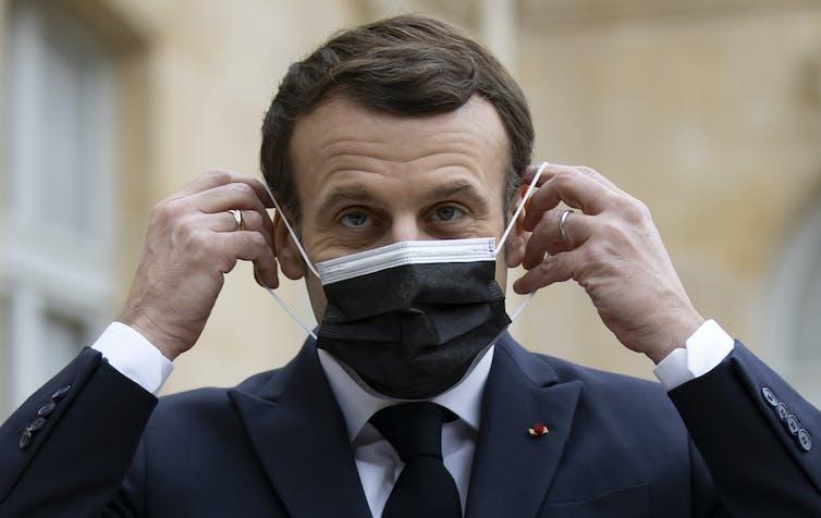 President  Emmanuel Macron putting a face mask on.