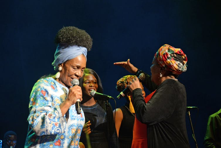 Four women on stage, two backing singers - who a woman instructs using a hand gesture and an elder woman foregrounded, singing into a microphone.