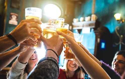 Happy people raising pints of beer in pub