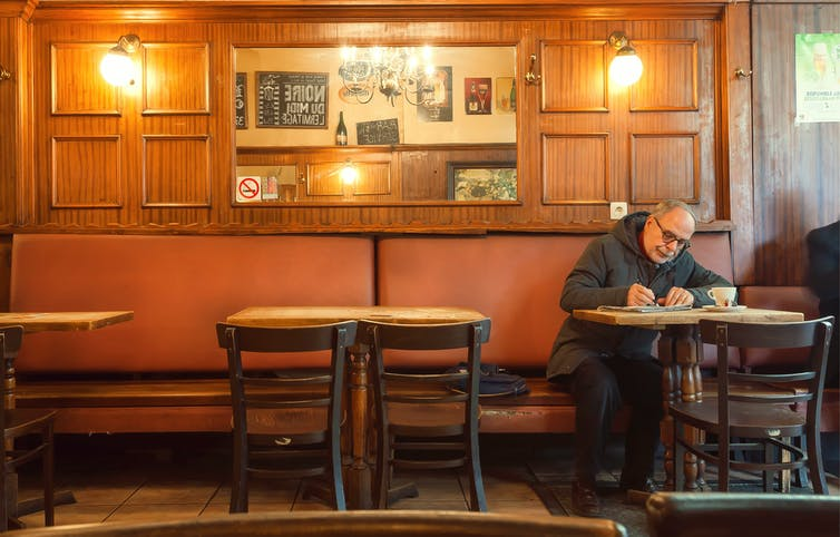 Man drinking alone at a table in a pub
