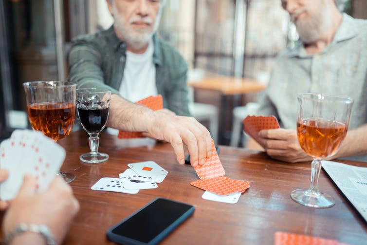 Bearded grey-haired men drinking alcohol and playing cards at a table with drinks