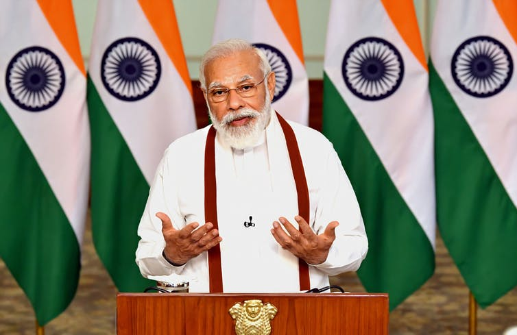Modi giving speech in front of Indian flags