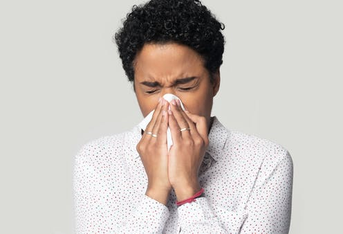 A woman sneezing into a handkerchief