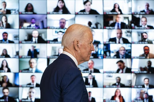 US president Joe Biden walks past a bank of screens showing a Zoom meeting with state department staff, February 4, 2021.