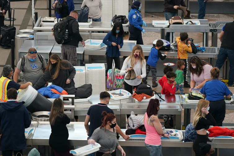 Travellers wearing face masks while pass through an airport security checkpoint.