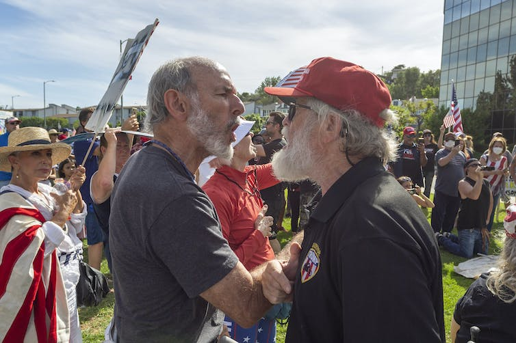 Two men at a protest about COVID-19 restrictions in California arguing with each other.