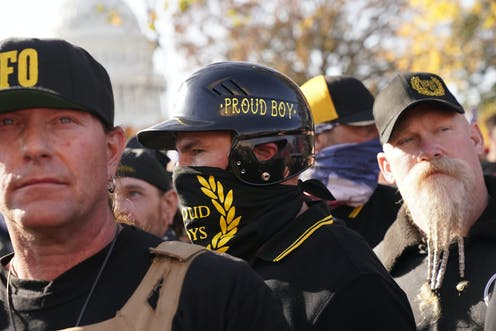 A man wearing a bandanna and hat with PROUD BOYS printed in yellow on black