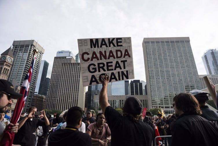 People at a protest holding a sign saying MAKE CANADA GREAT AGAIN