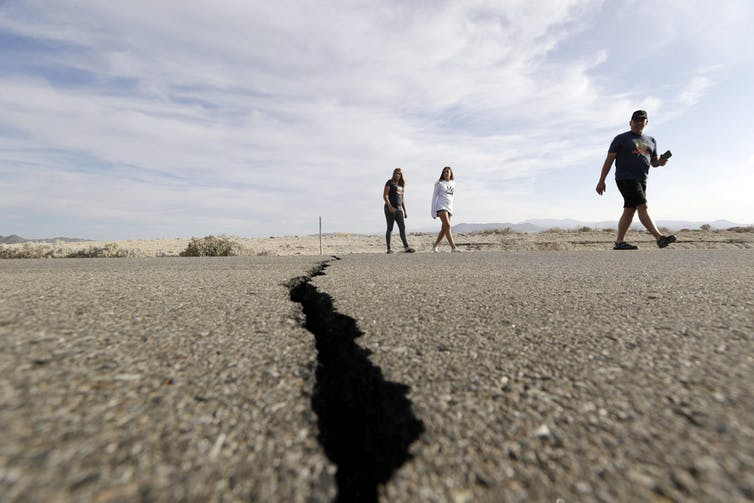 Visitors cross a highway with a large crack caused by an earthquake.