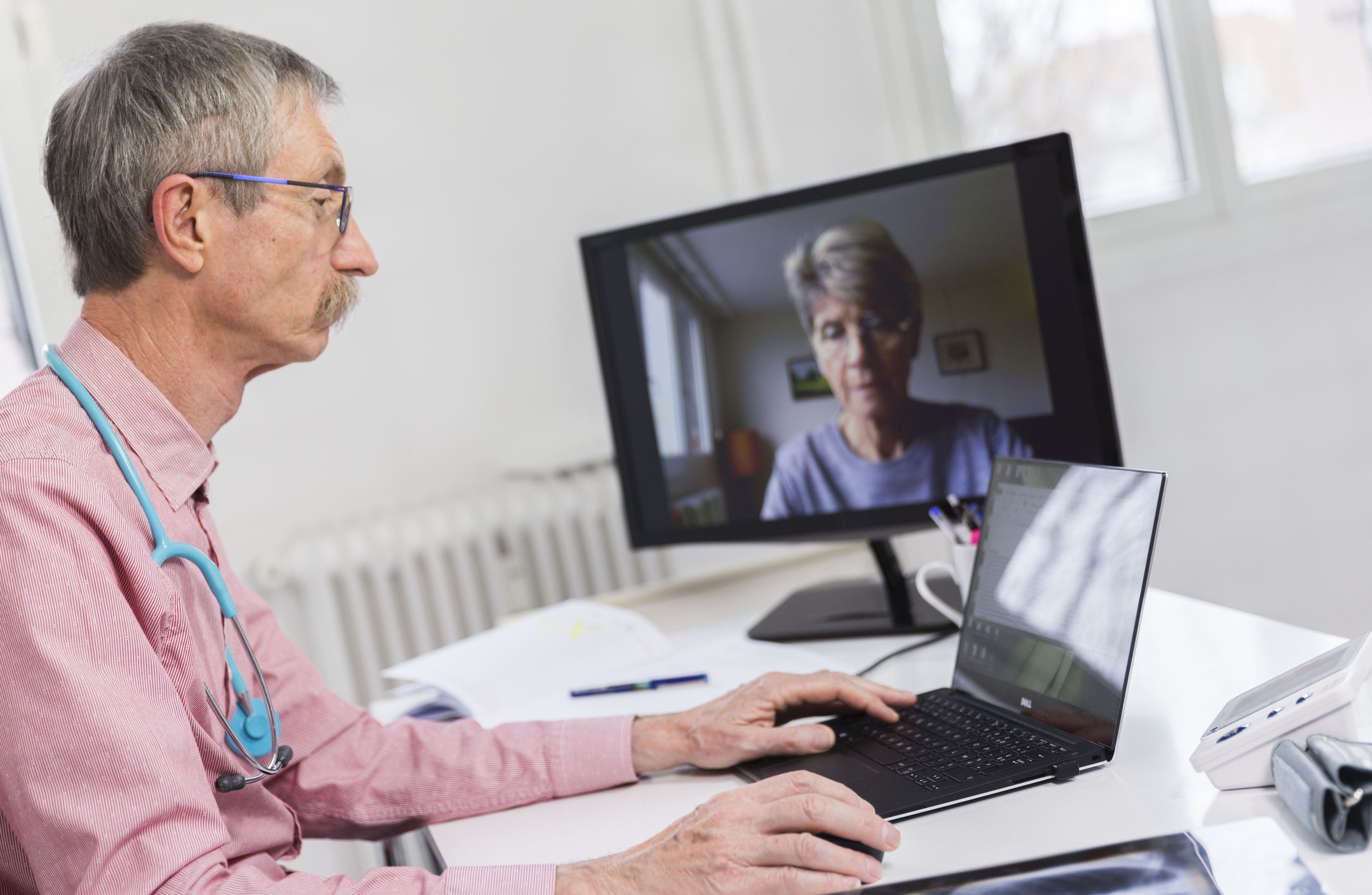 A doctor talks to a white patient through his laptop.