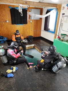 SCUBA divers sit around a square hole cut in Antarctic ice