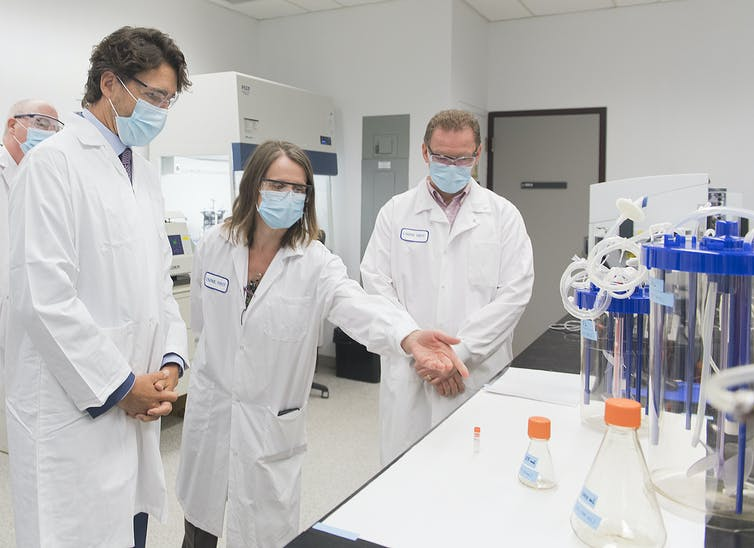 Trudeau and two scientists, all in white lab coats and face masks, in a lab