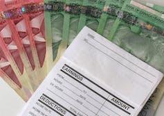 Canadian bills under a ledger.