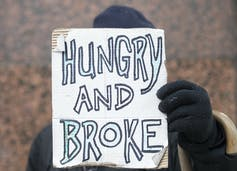 A homeless man holds up a sign reading Homeless and Broke.
