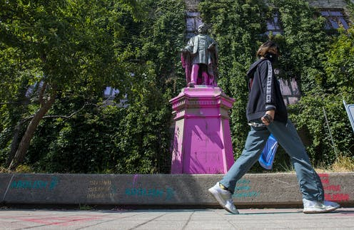 A person walks past Ryerson statue covered in paint.