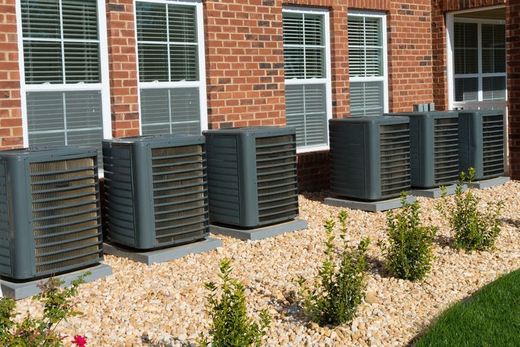 row of air conditioner units outside apartments