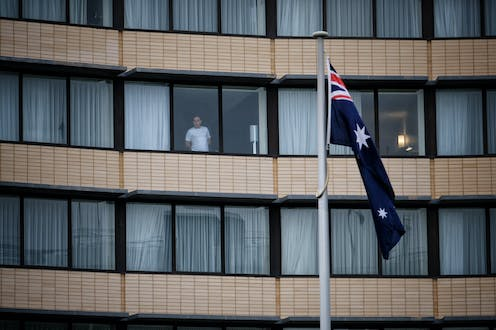 A guest is seen through the window at the Holiday Inn hotel at Melbourne Airport.