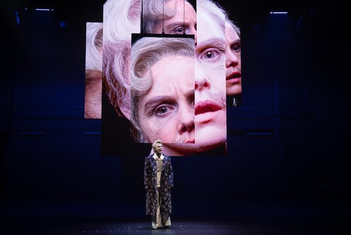 Woman onstage, with projected images behind her of her face.