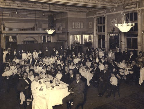 Crowd of men and women at a dinner.