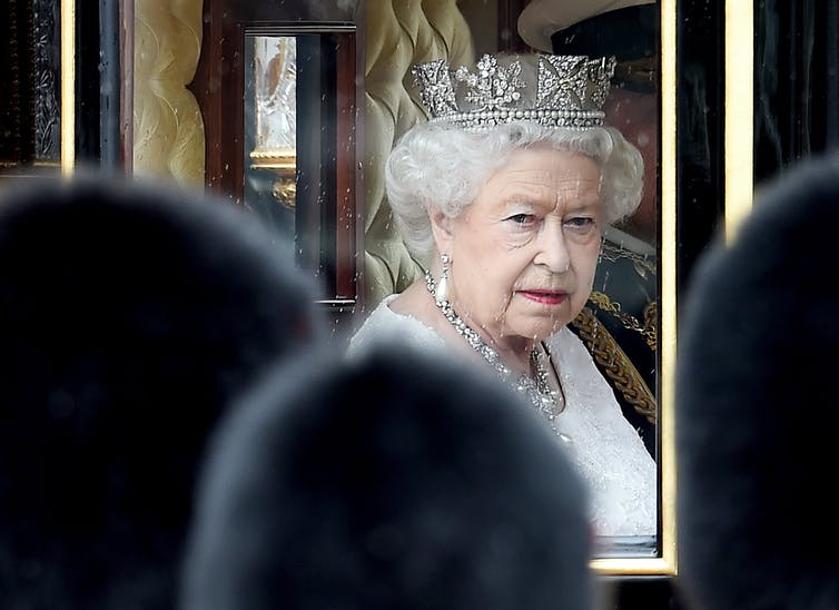 Queen Elizabeth riding in a royal carriage.