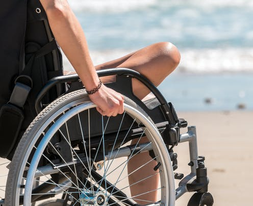 A person in a wheelchair at the seaside.