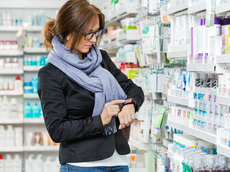 A woman in a pharmacy checks her smartwatch