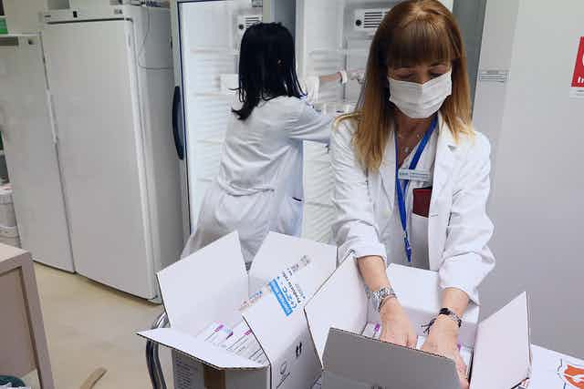 Spanish health workers filling fridges with doses of COVID vaccines