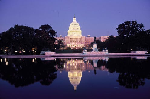 Photo of the Capitol at night with reflecting pool in the foreground