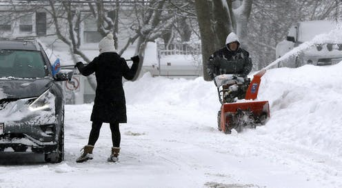 A woman scrapes snow off her car while a man uses a snowblower to clear his driveway.