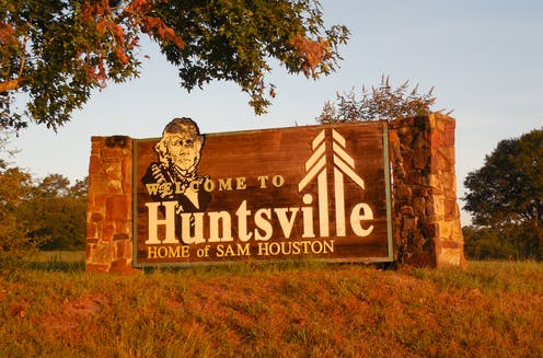 'Welcome to Huntsville, Home of Sam Houston' sign at the entrance of town, featuring the image of Sam Houston