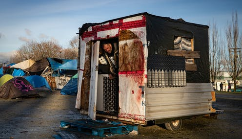 A man steps out of the trailer he lives in at a homeless encampment