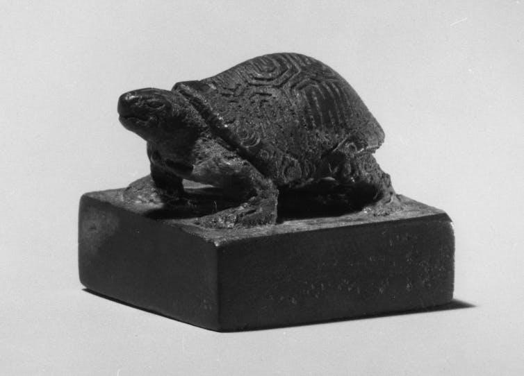Black sculpture of a tortoise.