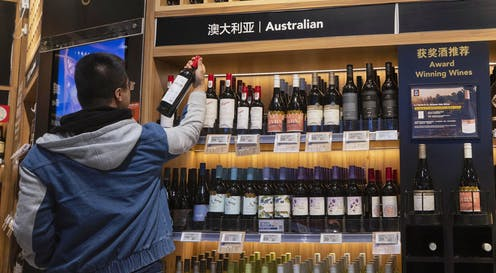 Chinese man examines an Australian wine in a bottle shop.