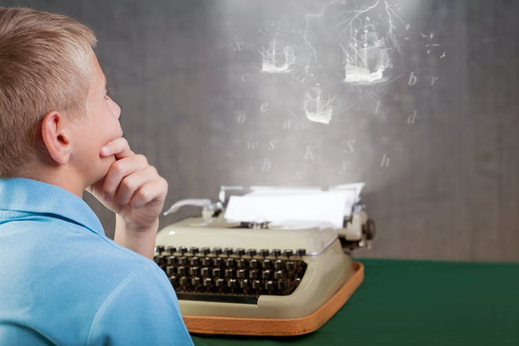 A young boy at a typewriting, imagining what he will write.