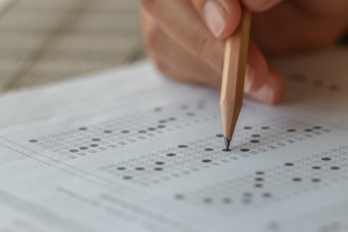 hand holding pencil over multiple choice test paper