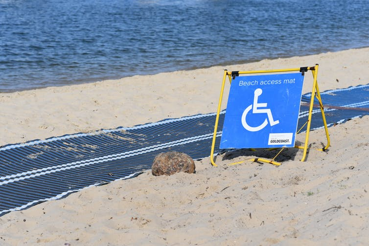 A long pathway mat on a beach with a disabled access sign.