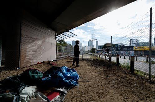 Homeless man looks out at the city from the underpass where he spent the night