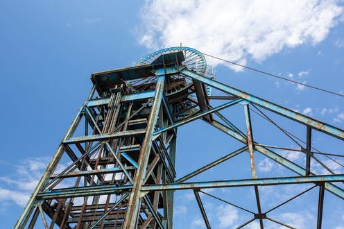 The rusty winding gear of a disused colliery.