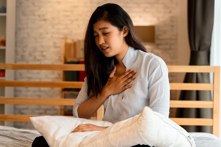 A woman sits on bed holding a pillow and touching her chest.