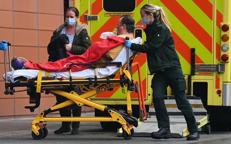 A man wearing on oxgen mask is wheeled into hospital by paramedics.