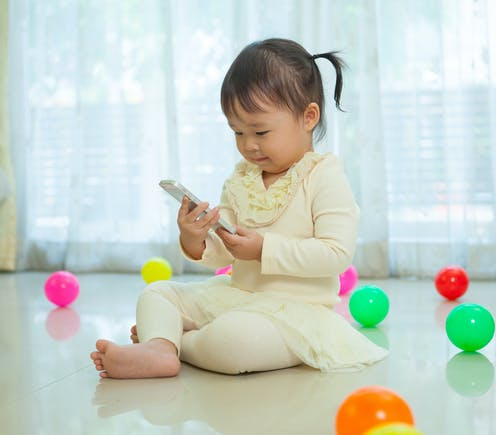 Toddler looking at mobile phone
