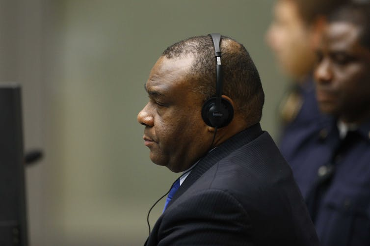 Jean-Pierre Bemba Gombo sits in headphones at the ICC during his war crimes trial.