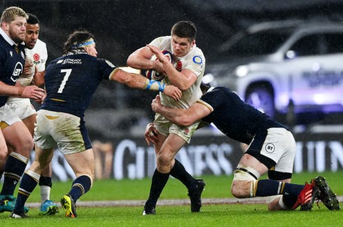 An England rugby player being tackled by Scotland players during a Six Nations match, February 2021.