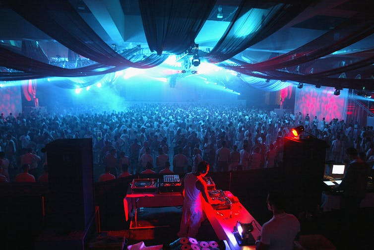 A DJ plays for a crowd dressed in white.