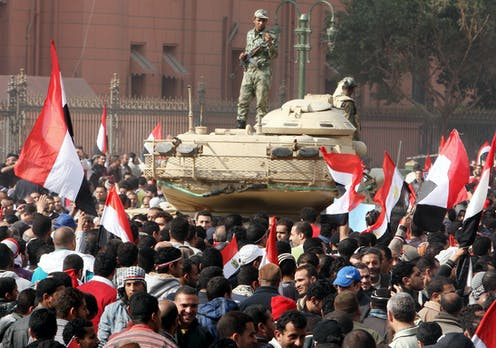 An Egyptian soldier stands on a tank in a square full of protesters waving the Egyptian flag.