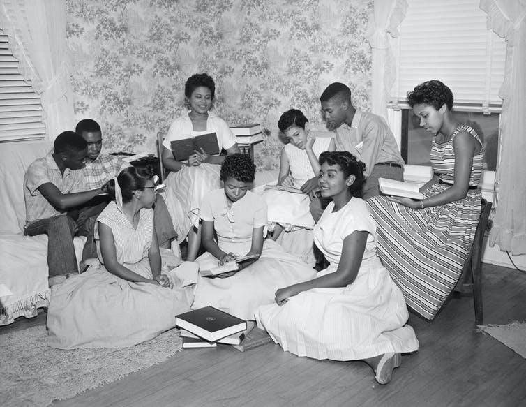 A group of African American students read books together in a small room.